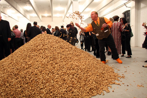 Jennifer Rubell, Creation, the Performa 09 Opening Night Benefit Dinner, 2009. Mario Batali throwing peanuts from the one-ton pile of nuts from Bazzini Nuts